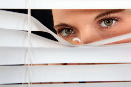 a blind: Woman peering through some blinds