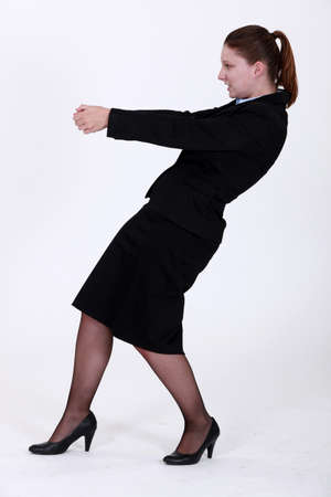 Businesswoman pulling an invisible object photo