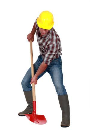power shovel: A male construction worker using a shovel.