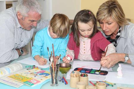 Enkelkinder Zeichnen und Malen unter Großeltern Standard-Bild