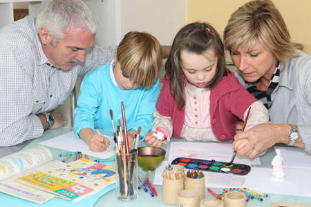 family activities: grandchildren drawing and painting under grandparents
