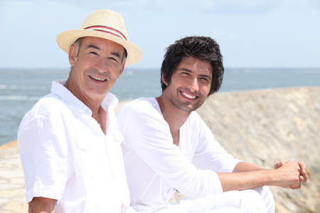 65 years old: 65 years old man and a 30 years old man sitting on the sand with background of sea