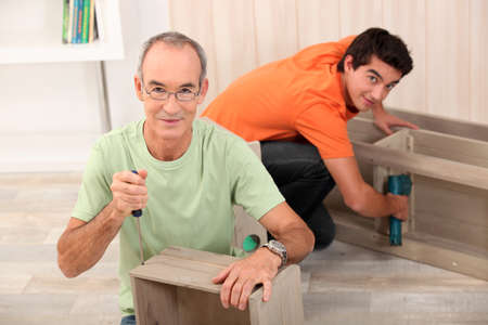 college dorm: Father and son assembling furniture