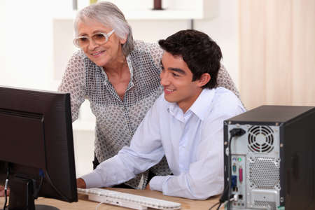 Young man helping his grandma with her computer. photo