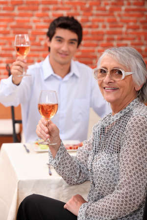 Grandmother and young man drinking rose wine photo