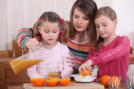 pour water: Little girls making orange juice Stock Photo