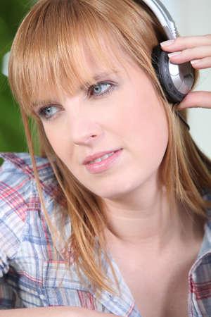 dreamy eyed: young woman wearing earphones Stock Photo