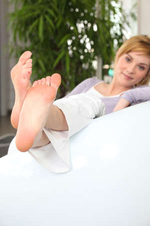 bare feet: Young woman on a sofa looking at her bare feet Stock Photo