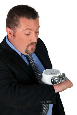 high powered: businessman looking at his enormous hand watch