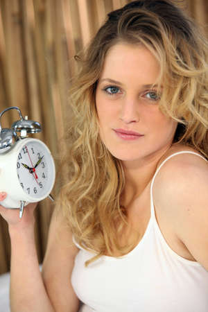 Woman holding alarm clock photo