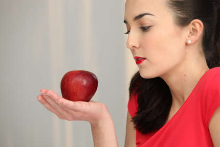 mesmerized: Woman holding a red apple in the palm of her hand