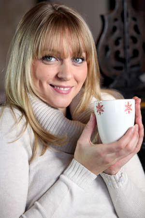 Portrait of a blonde woman drinking a hot drink photo