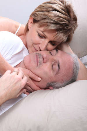 Senior couple laid in a bed photo
