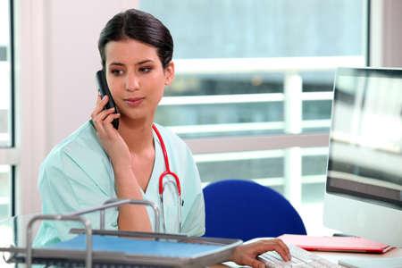 maligno: joven enfermera en el tel�fono detr�s de su equipo