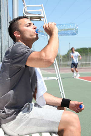 municipal court: Man drinking water on tennis court sideline Stock Photo