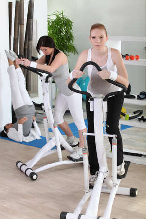 Women using stepper machine in gym photo
