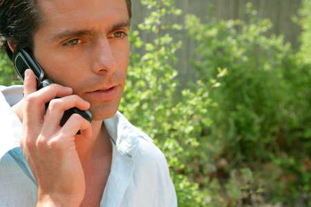 man on the phone outdoors looking concerned photo