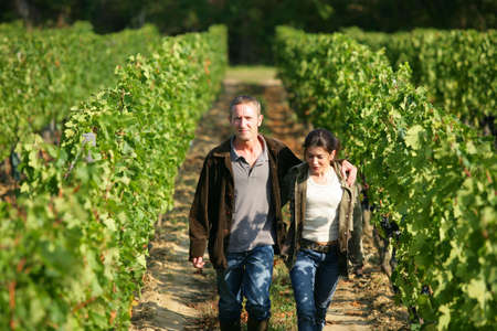 couple walking in their vineyard photo