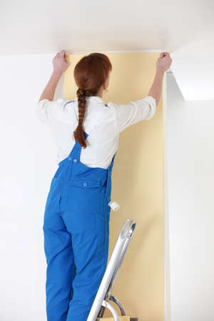 putting up: Woman putting up yellow wallpaper Stock Photo