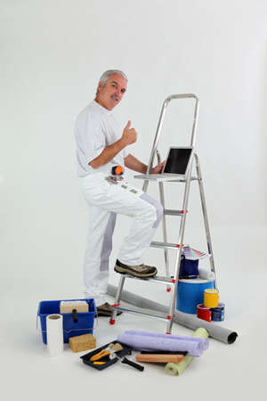 decorator: Male decorator with ladder giving thumbs-up Stock Photo