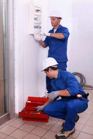 meter box: dos electricistas de trabajo, uno es el establecimiento de un contador de electricidad