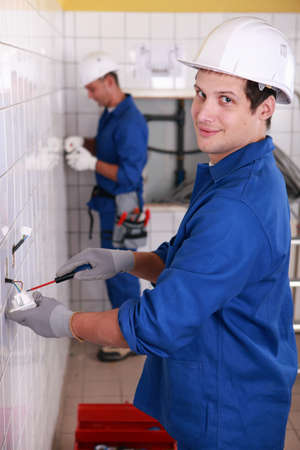 Young electricians wiring wall sockets Stock Photo - 12218535