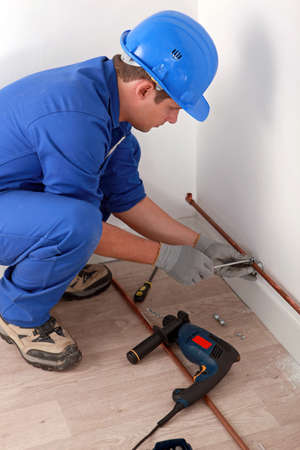 Plumber fixing copper pipe to wall photo