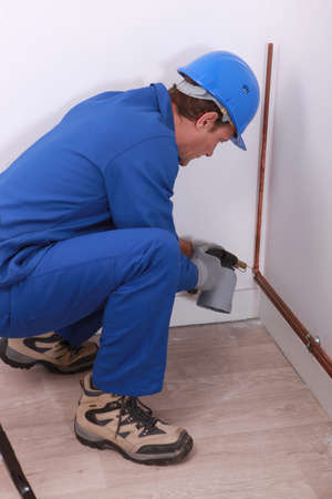 blowtorch: A plumber at work with a blowtorch. Stock Photo