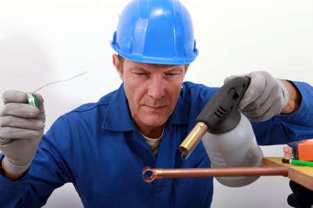 koperen leiding: ambachtsman solderen van een koperen buis Stockfoto