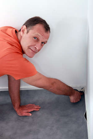 exact position: Man laying down linoleum flooring