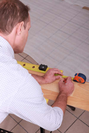 Worker marking a measurement on a plank of wood photo