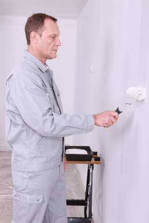 40 45: Male decorating painting a room white