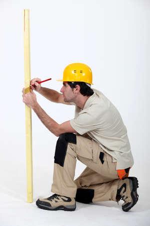 arrodillarse: Comerciante marcando una medición en una tabla de madera