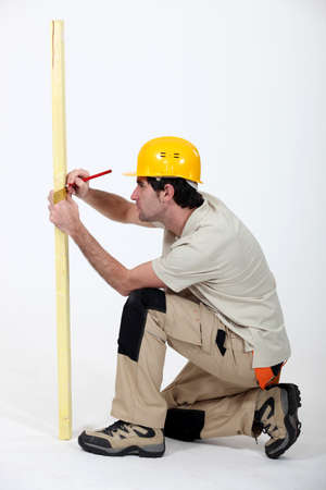 Tradesman marking a measurement on a wooden plank Stock Photo - 12218181