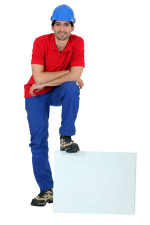 1 person: craftsman leaning his foot on a blank box Stock Photo