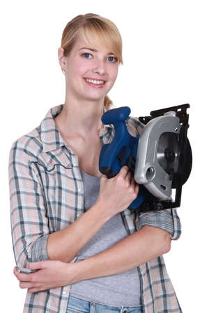 Smiling young woman holding circular saw photo