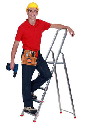 Man with drill standing on ladder rung photo