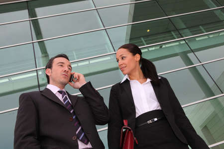 Pair of execs using a cellphone outside an office building photo