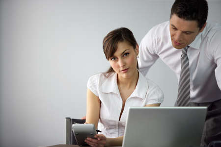 employee at her desk with colleague Stock Photo - 12217964