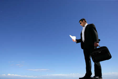 brief case: Businessman with a briefcase against a blue sky Stock Photo