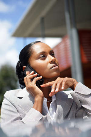 ebony: Pensive businesswoman making a call outdoors Stock Photo
