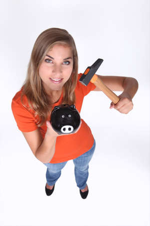 Teenage girl holding piggy bank and hammer photo