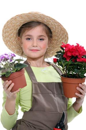 Little girl holding flower pots photo