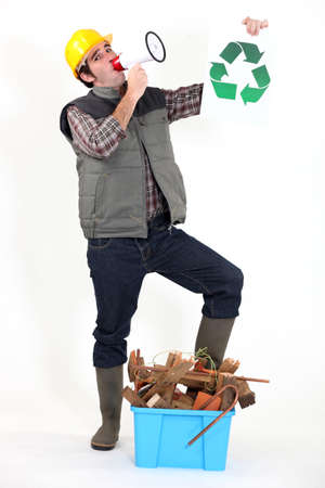 portrait of carpenter with loudspeaker and recycling logo photo