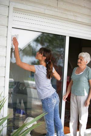 cleaning window: Donna delle pulizie una porta finestra di vetro per una signora anziana Archivio Fotografico