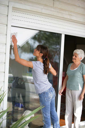 Woman cleaning a glass patio door for an elderly lady photo