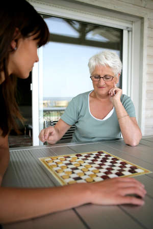 chess player: Young woman and senior woman playing checkers