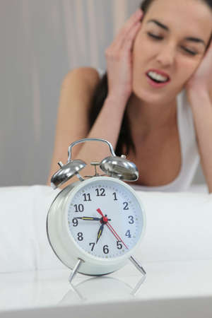 Unhappy woman shutting out the noise of her alarm clock Stock Photo - 12218323