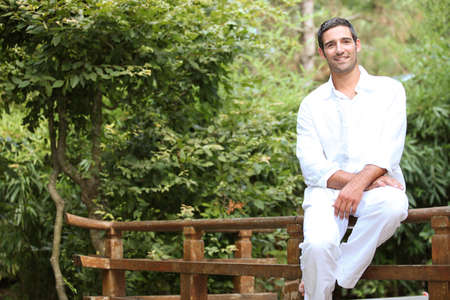untroubled: Man sitting on a Japanese style wooden fence Stock Photo