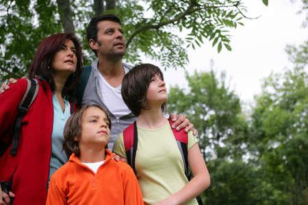 una familia en el bosque mirando hacia arriba